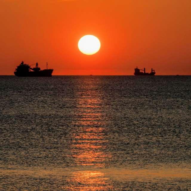 船の間に日が沈む