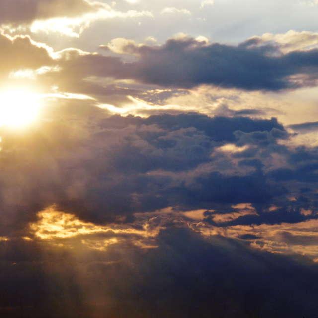 Солнце смотрит из-за облаков.