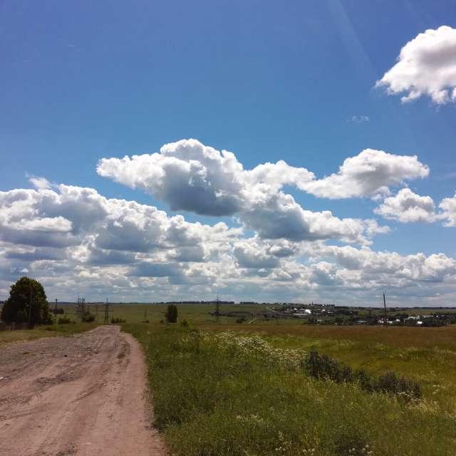 Дорога в поле с облаками