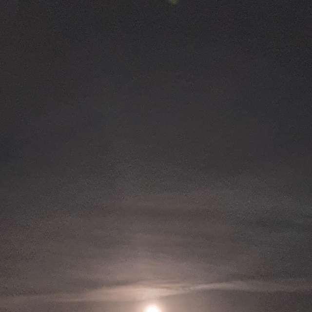 Full moon between clouds