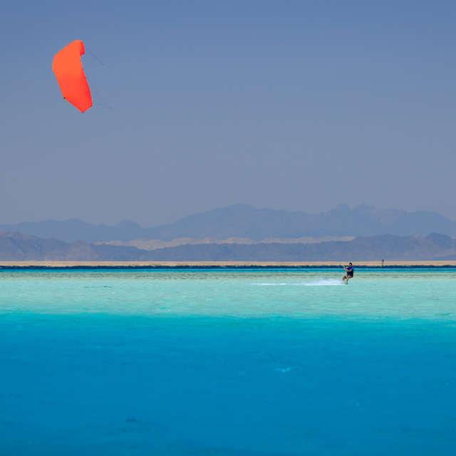 Kiter with orange kite in sea