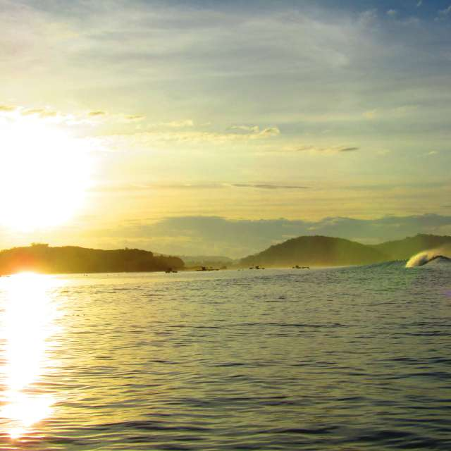 眩しい朝日と波
