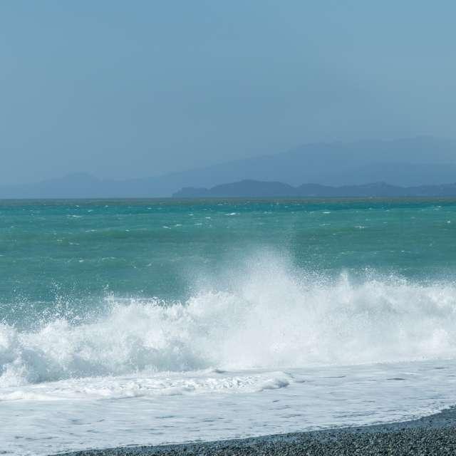 高波の浮か打ち付ける海岸の向こうに真鶴半島と伊豆が