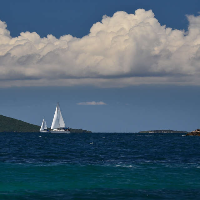 Sailboat under white clouds