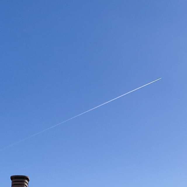 Cielo azul con estela avión.