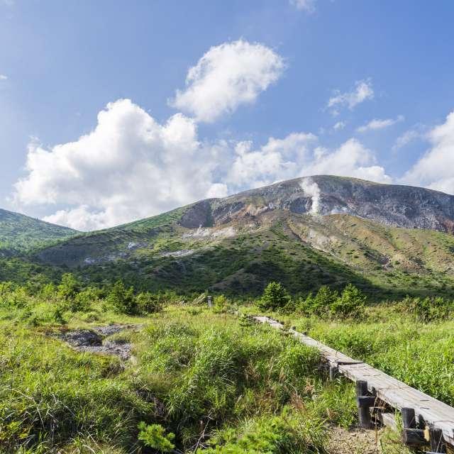 湿原(浄土平)の木道と噴煙を出す火山(吾妻山)