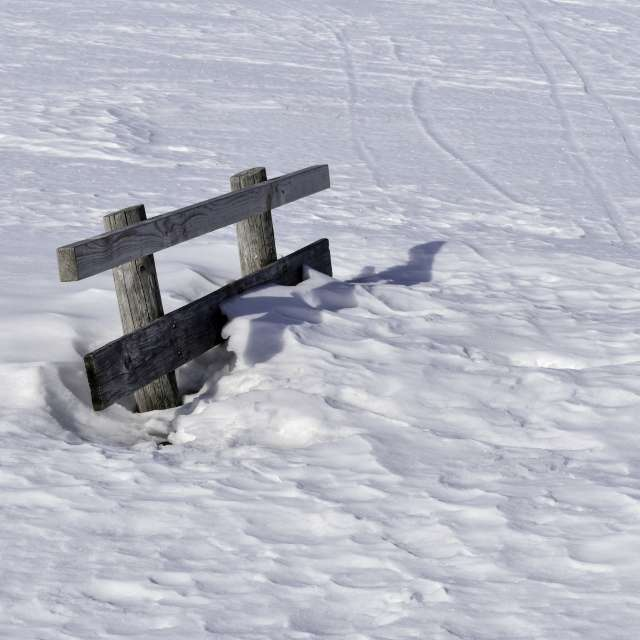 Wooden bench in snow.